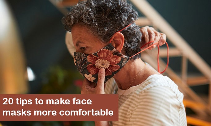 woman with dark curls adjusts cloth face mask to make it more comfortable