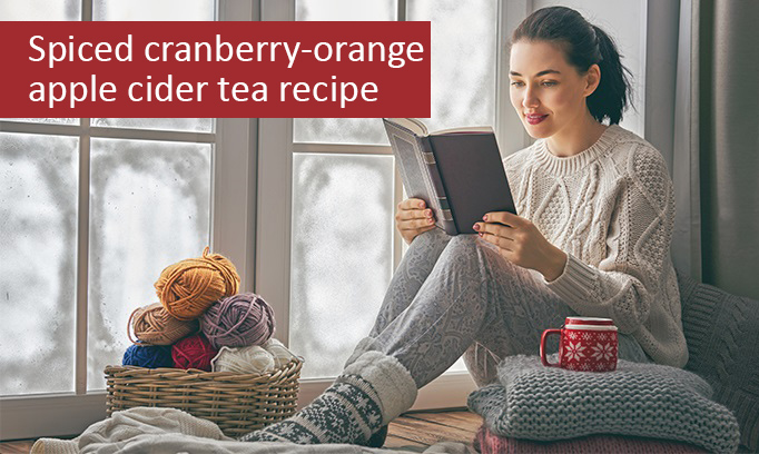 Young woman sitting in a window seat drinking spiced cranberry-orange apple cider tea while reading a book during the winter.
