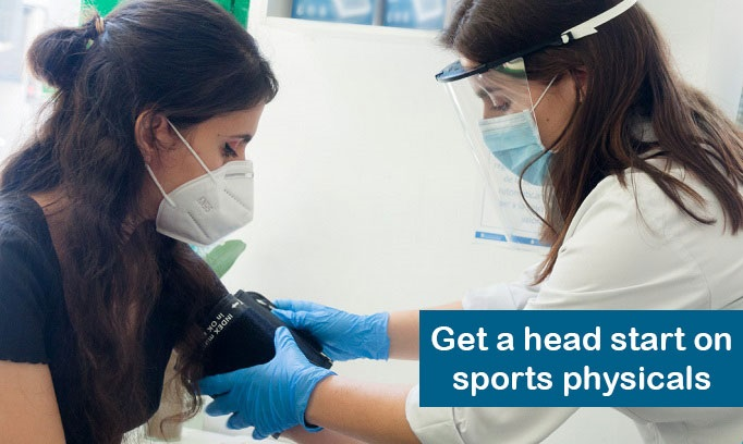 teen girl with long dark hair wearing face mask has BP taken as part of a sport physical by female doctor