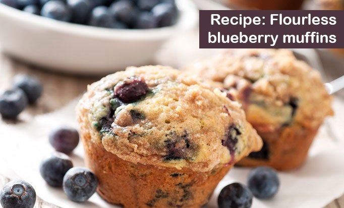 two blueberry muffins with big white bowl of blueberries and scattered blueberries